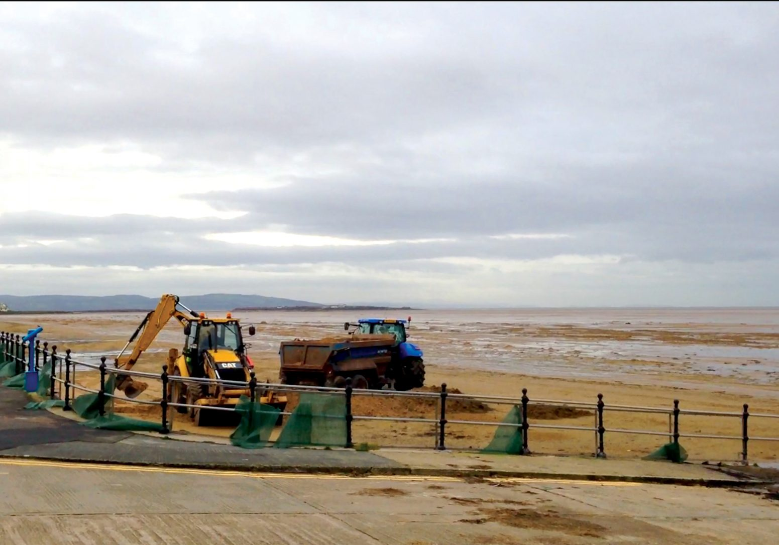 December 2014. Mechanical lowering of sand levels at the promenade wall. Ongoing sand accretion threatens to block surface water drainage. © HVL